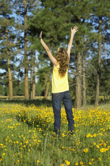 Young woman raising hands in a field of wildflowers