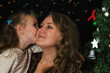 Little girl kissing her mother in christmas time