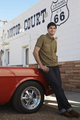 Young man leaning on car by motel, Arizona, USA