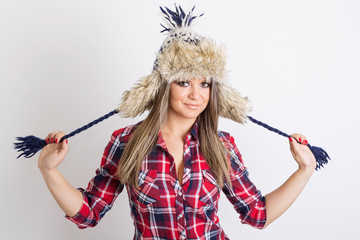 Cute fashionable young woman wearing fluffy winter hat