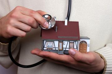 Haus wird mit Stetoskop abgehört, Hauskauf