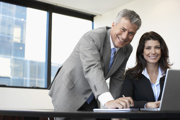 Two businesspeople working on laptop