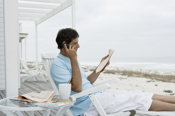 Mid adult man reading newspaper and using mobile phone near beach