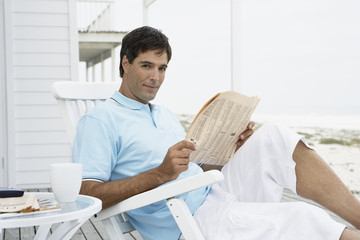 Mid adult man reading newspaper on lounge chair
