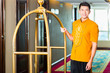 Asian bell boy or porter bringing suitcase to hotel room