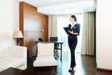 Asian executive housekeeper controlling hotel room