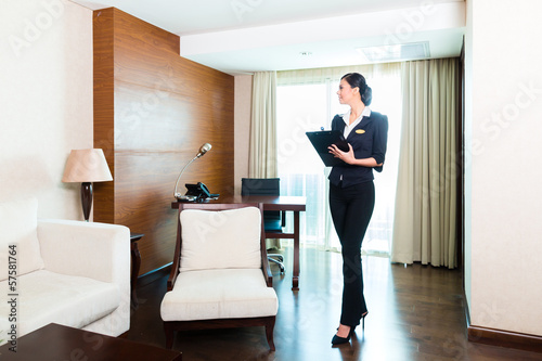 Asian executive housekeeper controlling hotel room - 57581764