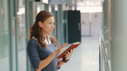 business woman with tablet computer in office building