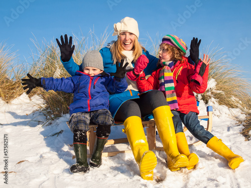 young family portrait sitting on a wooden sledge