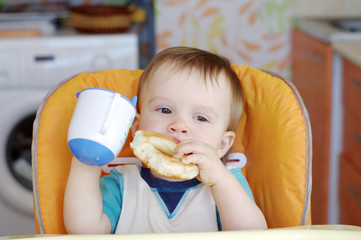 baby with round cracknel and cup of tea