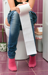 Woman in a toilet with a big hank of sanitary paper