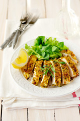 Sliced lemon herb crusted chicken breast, copy space for your te