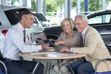 Salesman and couple viewing brochure at table in car dealership showroom