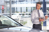 Smiling salesman with brochure leaning on car in car dealership showroom