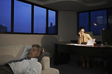Businesswoman Working Late, Man Sleeping on Sofa in Office