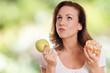 Frau überlegt Apfel oder Gebäck