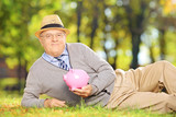 Smiling mature gentleman on grass holding a piggy bank