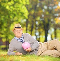 Satisfied mature gentleman in a park holding a piggy bank