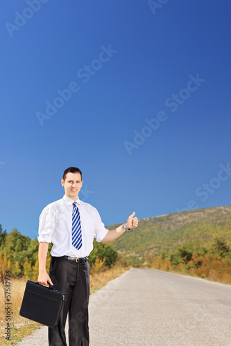 Young businessperson holding a suitcase and hitchhiking on road