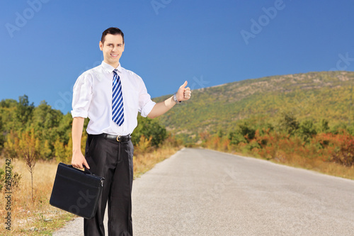 Young businessperson holding a leather suitcase and hitchhiking
