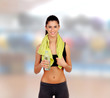 Woman in fitness with a towel drinking water