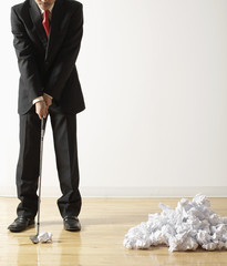 Businessman Playing Golf with Crumpled Paper