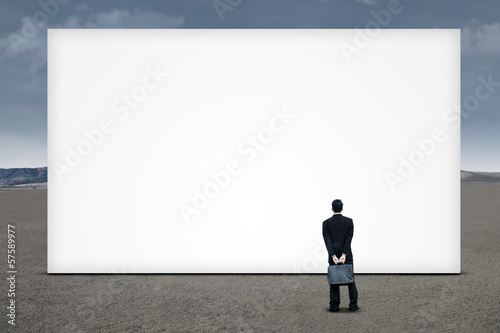 Businessman is looking at empty board