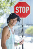 Portrait of smiling young man wearing headphones and using digital tablet near stop sign in city