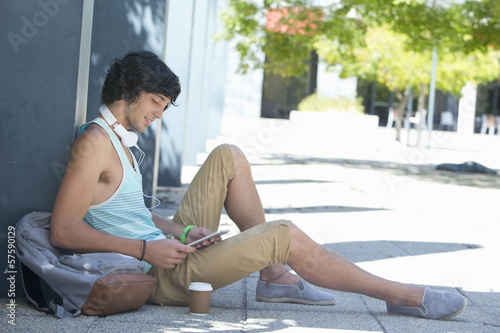 Young man with backpack, coffee cup and headphones using digital tablet on sidewalk