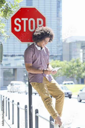 Young man wearing headphones and using digital tablet against stop sign in city