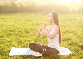 girl in lotus pose at sunset