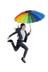 Happy businesswoman jumping with umbrella