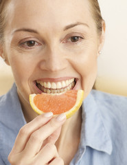 Mid-Adult Woman Eating Slice of Orange