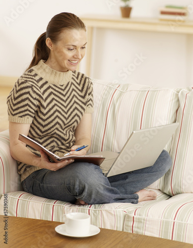 Mid-Adult Woman Using Laptop and Making Notes