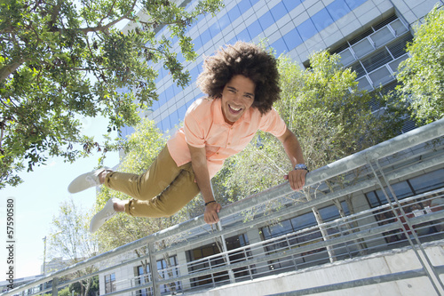 Smiling young man jumping over railing in city