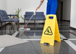 Leinwanddruck Bild - Man With Mop And Wet Floor Sign