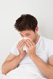 Man Sneezing Into A Tissue
