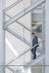 Businessman descending stairs in office