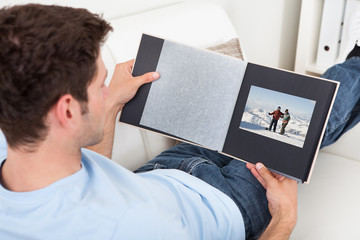 Young Man Looking At Photo Album