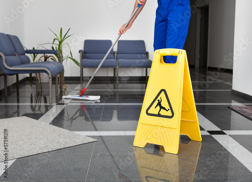 Leinwanddruck Bild Man With Mop And Wet Floor Sign