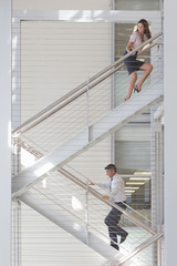 Businessman and businesswoman on stairs in office