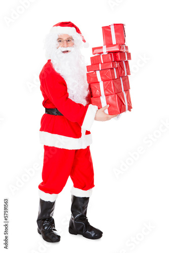 Portrait of santa holding stack of gift