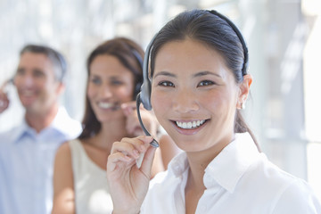 Close up portrait of smiling businesswoman wearing headset