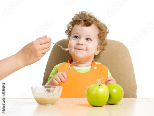 mother hand spoon feeding baby boy
