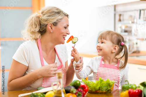 kid daughter feeding mother vegetables in kitchen