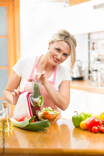 Cute woman cutting vegetables with device at the kitchen table