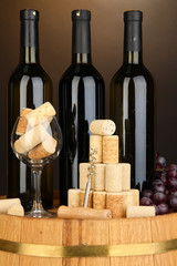 Wine and corks on barrel on brown background