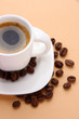 Cup of coffee with coffee beans on beige background