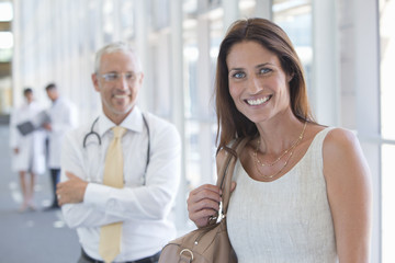 Close up portrait of smiling patient with doctor in hospital corridor