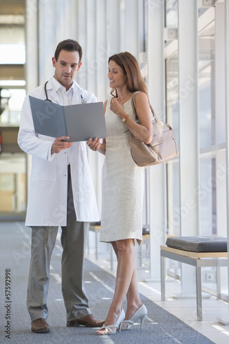 Doctor and patient reviewing medical chart in hospital corridor